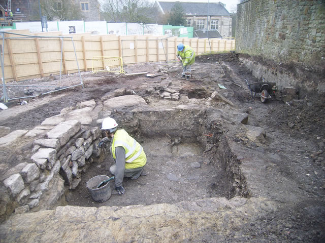 archaeologist cleaning a wall face uncovered during the excavation at keynsham